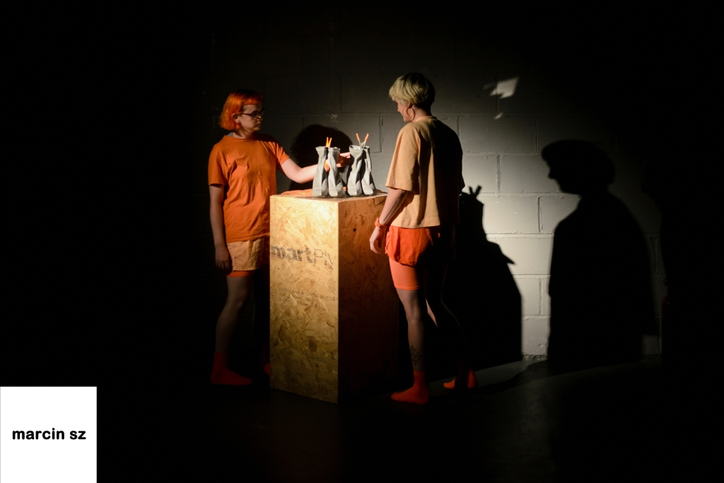 Emily and Emily stand in a spotlight next to a wooden plinth. On it are two pairs of reflective heeled boots.