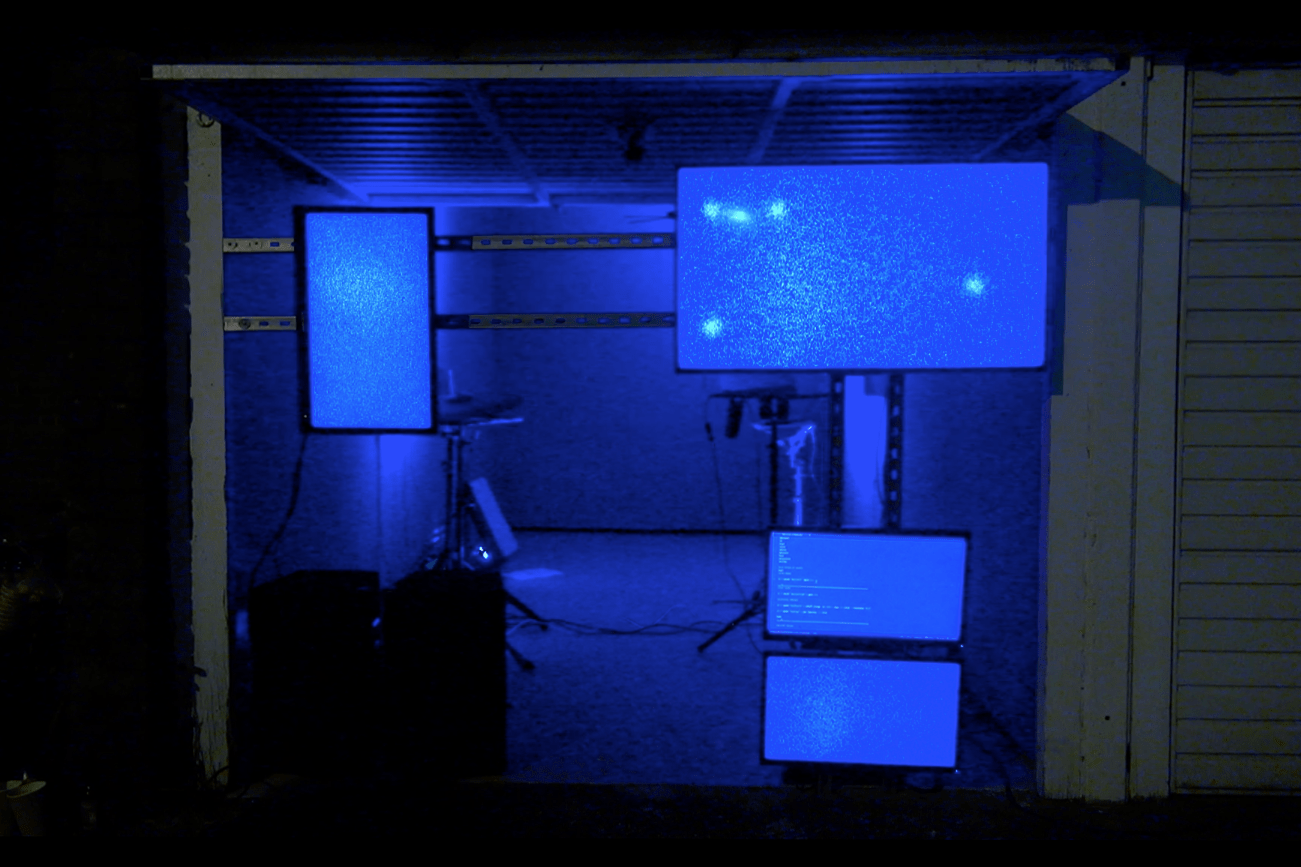 A garage is filled with blue light. Screens suspended on a metal track are hung in the open doorway to the garage. Each of the four screens are blue.