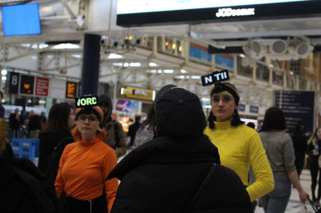 Two performers are wearing phones attached to their head. They are both looking into the camera wearing yellow and orange.