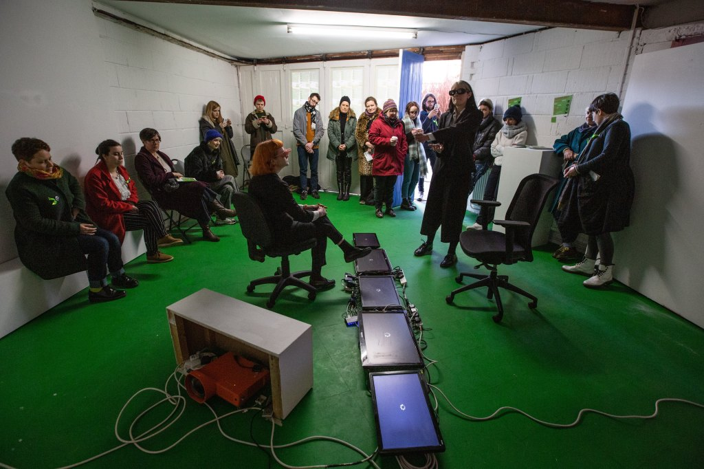 A room full of people surround two performers dressed in suits. There is a line of screens that divide the space on the floor.