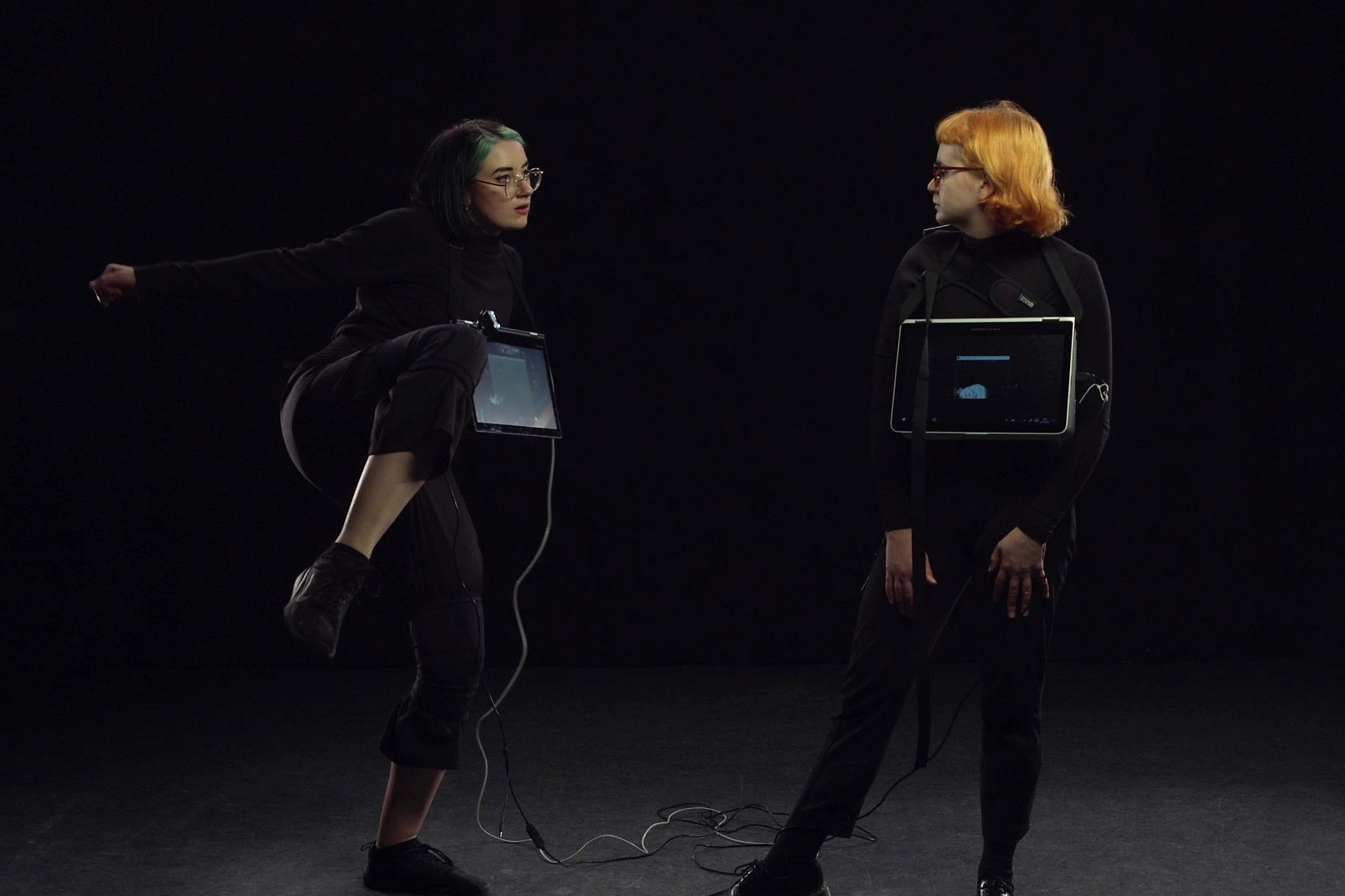 Two performers have screens attached to their chests. They are dressed in black, facing eachother in a dark room.